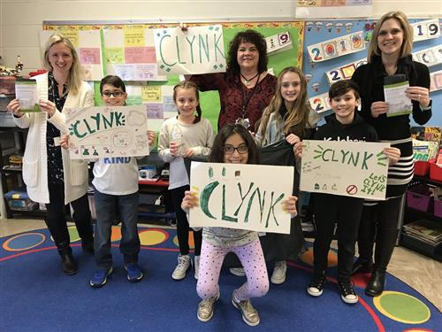 A group of elementary students and their two teachers holding signs that say CLYNK
