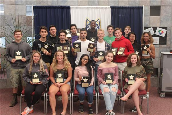 Group of 22 students holding plaques