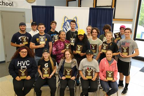 Senior athletes show their plaques off at an awards ceremony.