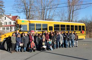 The transportation team posing for a photo in front of a school bus.