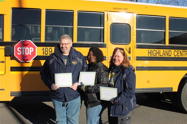 Three bus drivers with certificates of appreciation standing in front of a school bus