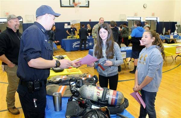 Two students speak with a first responder.