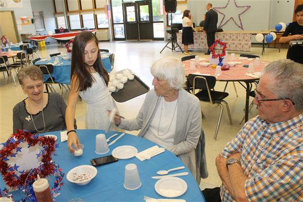 Young student serving dinner to senior citizens